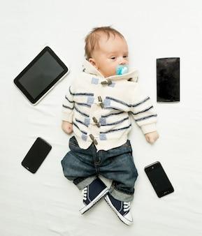 Menino fofo deitado na cama com tablets e smartphones digitais