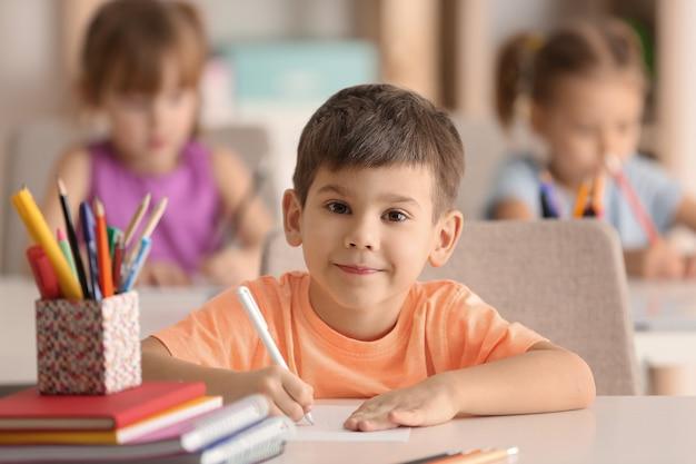 Menino fofo desenho na sala de aula