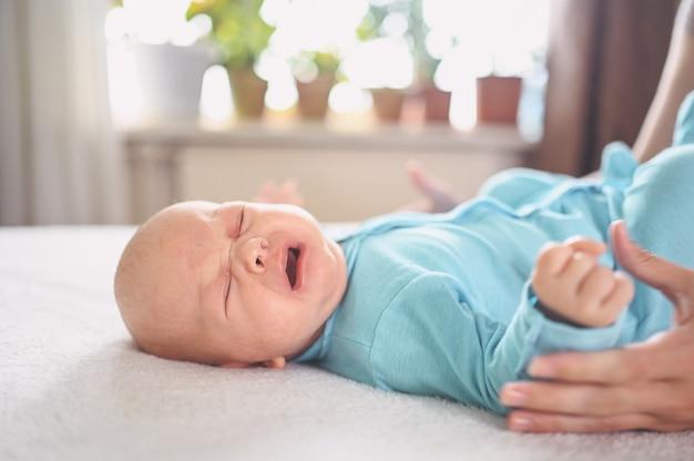 Menino fofo e emocional recém-nascido chorando em macacão azul, deitado na cama expressões faciais de bebê.
