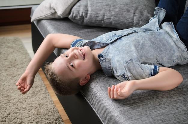 Menino fofo e engraçado deitado de cabeça para baixo no sofá olhando para a câmera sorrindo brincalhão menino se divertindo em casa