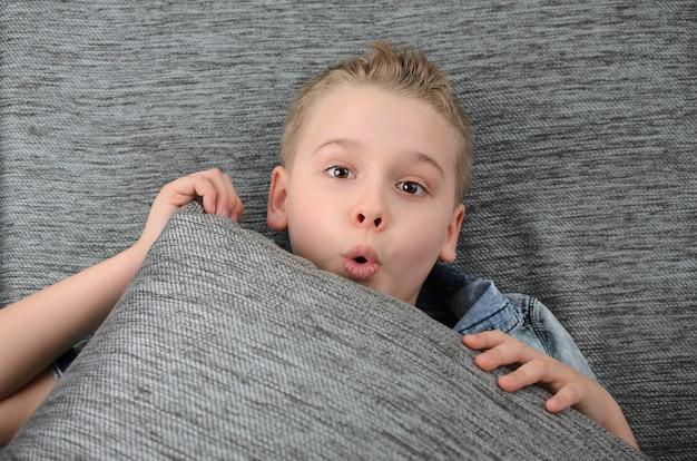 Menino fofo e engraçado está deitado de costas no sofá e fazendo careta brincalhão menino se divertindo em casa Foto Premium