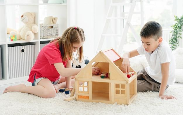 Menino fofo e menina brincando dentro de casa Foto Premium