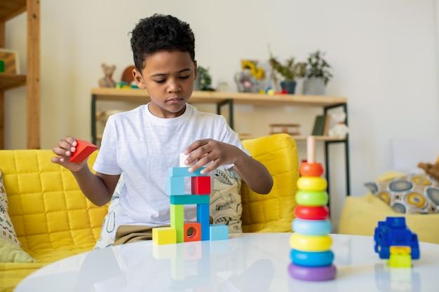 Menino fofo e sério de idade elementar construindo uma torre ou casa de vários andares com cubos de brinquedo na mesa enquanto está sentado no sofá amarelo em casa