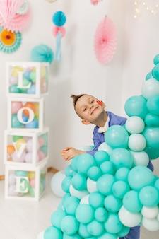 Menino fofo e sorridente com um coração vermelho na bochecha espiando por trás de balões de festa coloridos
