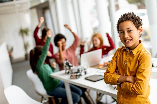 Menino fofo em frente a um grupo de crianças programando brinquedos elétricos e robôs na sala de aula de robótica