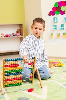 Menino fofo em idade pré-escolar brincando com um ábaco de madeira