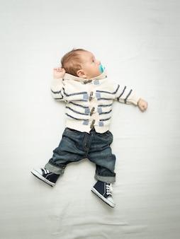 Menino fofo em jeans segurando uma chupeta, deitado na cama