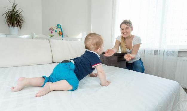 Menino fofo engatinhando na cama para a jovem mãe feliz