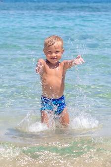 Menino fofo engraçado feliz brincando nas ondas de água no mar oceano em um dia ensolarado