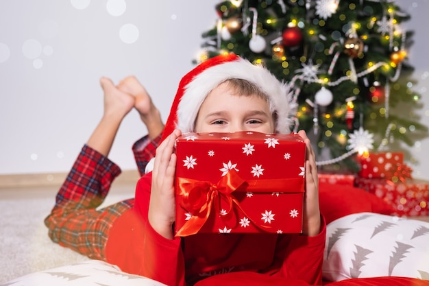Menino fofo feliz com chapéu de papai noel segurando uma caixa de presente festiva e deitado no chão perto da árvore de natal