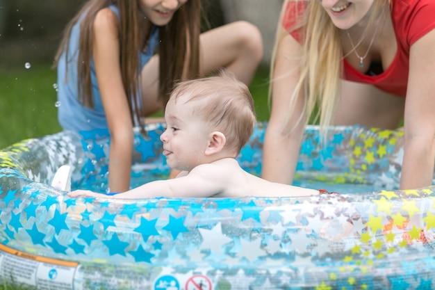 Menino fofo nadando na piscina ao ar livre com a mãe e a irmã
