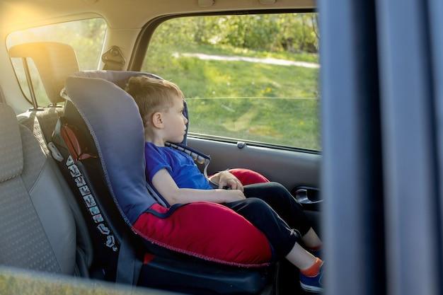 Menino fofo pré-escolar de 3 a 4 anos sentado na cadeirinha do carro chorando durante uma viagem de carro em família
