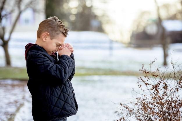 Menino fofo rezando de olhos fechados no meio do parque de inverno