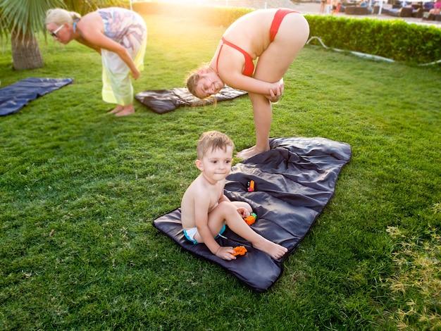 Menino fofo sentado ao lado da mãe de biquíni fazendo exercícios de ioga na praia