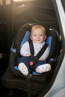 Menino fofo sentado na cadeira de criança no carro
