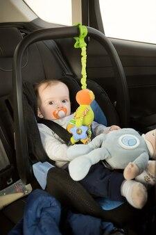 Menino fofo sentado na cadeirinha do carro brincando com brinquedos
