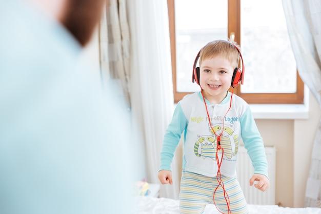 Menino fofo sorridente com fones de ouvido vermelhos, em pé na cama e ouvindo música