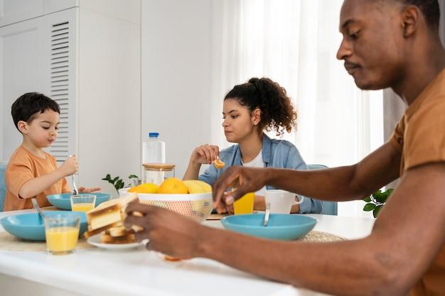 Menino fofo tomando café da manhã com os pais