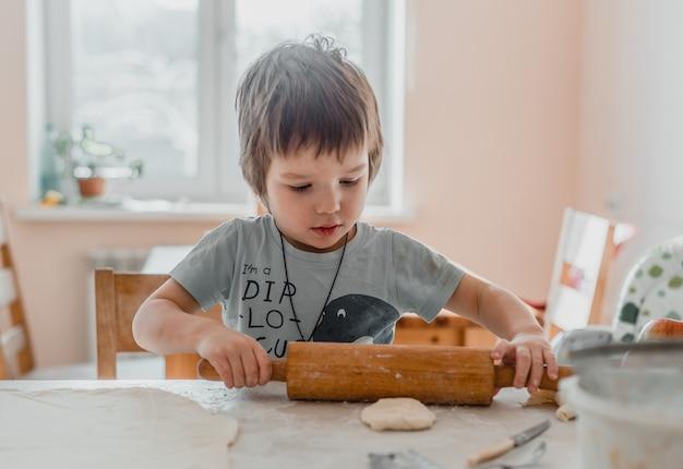 Menino fofo usando o rolo de massa para preparar a massa para biscoitos na cozinha