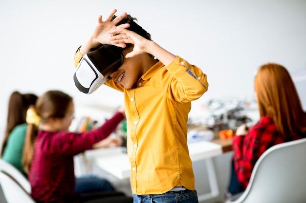 Menino fofo usando óculos de realidade virtual em uma sala de aula de robótica