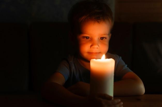 Menino garoto admira uma vela acesa de cera à noite em casa