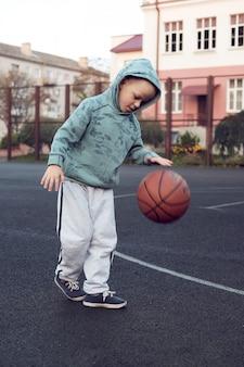 Menino garoto jogando basquete na quadra de streetball