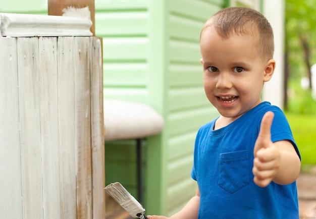 Menino garoto sorridente, pintando móveis de madeira com pincel e desistir de polegar