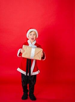 Menino garoto vestido de papai noel. compras de natal. presente de natal. infância