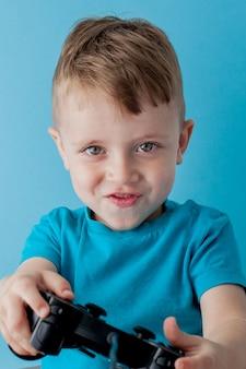 Menino garoto vestindo roupas azuis segurar joystick na mão para gameson fundo azul