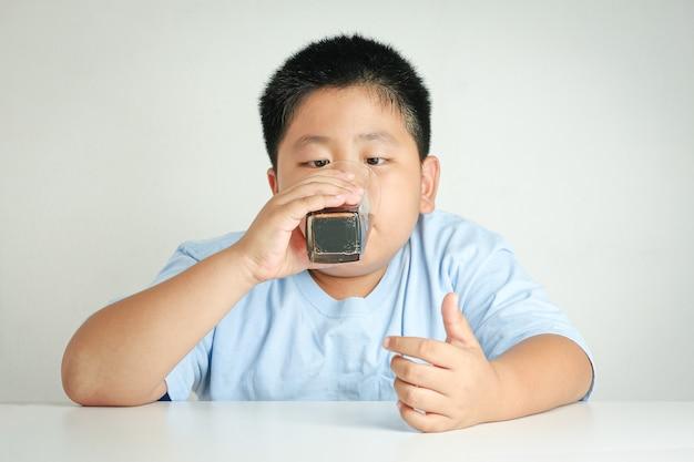 Menino gordo comendo o corpo acumula açúcar. a obesidade não é boa para a saúde.