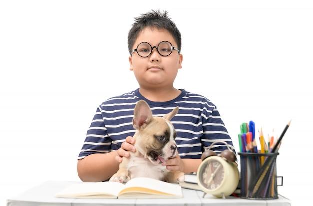 Menino gordo jogando bonitinho pequeno bulldog francês na mesa