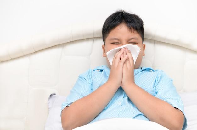 Menino gordo tem corrimento nasal e assoa o nariz no tecido