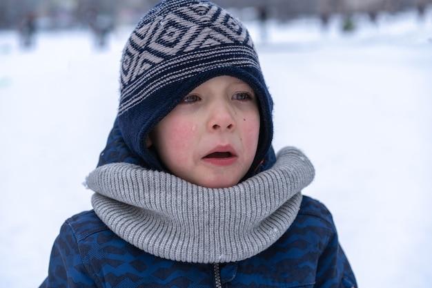Menino grita e chora. emoções. menino com roupas de inverno