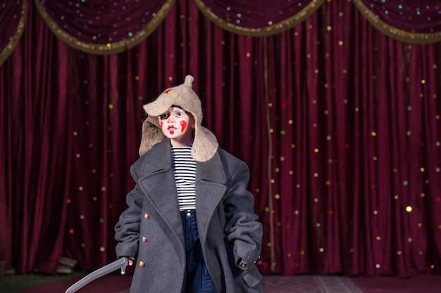 Menino habilidoso e empático fingindo ser um bravo soldado russo durante uma atuação dramática, no palco, contra cortinas clássicas vermelho-escuras