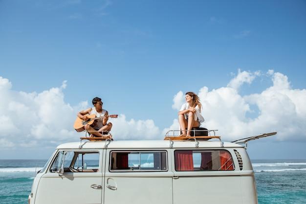 Menino hippie tocando violão com a namorada em cima do estilo retrô