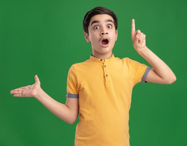 Menino impressionado apontando para cima mostrando a mão vazia olhando para frente isolada na parede verde