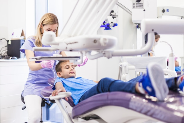 Menino, inclinar-se, cadeira dental, obtendo, tratamento, por, femininas, odontólogo