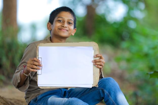 Menino indiano / asiático bonitinho mostrando bloco de notas com caneta