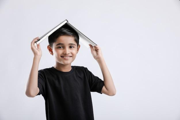 Menino indiano / asiático com livro na cabeça e pensando seriamente