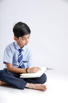 Menino indiano / asiático escola bonitinha com óculos lendo livro
