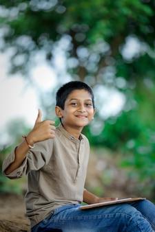Menino indiano / asiático mostrando o polegar para cima