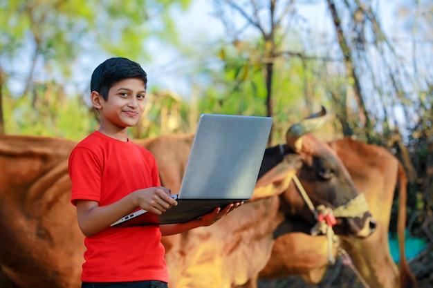 Menino indiano / asiático pequeno bonito estudando ou jogando o jogo com o computador portátil