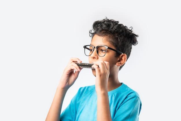 Menino indiano asiático tocando gaita ou órgão da boca, conceito de aprendizagem precoce