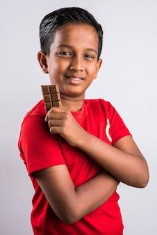 Menino indiano bonitinho comendo chocolate, isolado no fundo branco,
