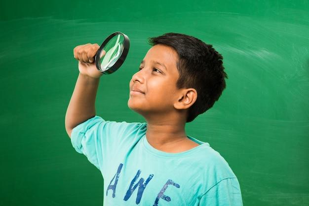 Menino indiano de escola asiática segurando uma lupa em pé, isolado sobre o fundo verde do quadro-negro