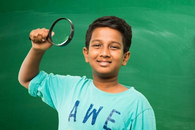 Menino indiano de escola asiática segurando uma lupa em pé, isolado sobre o fundo verde do quadro-negro Foto Premium