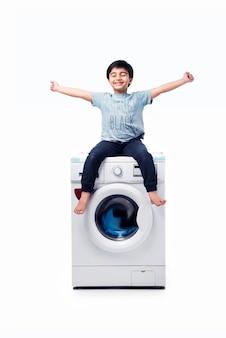 Menino indiano feliz posando com a máquina de lavar ou a máquina de lavar louça contra um fundo branco
