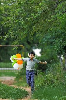 Menino indiano fofo com balões tricolores e comemorando o dia da independência ou da república da índia
