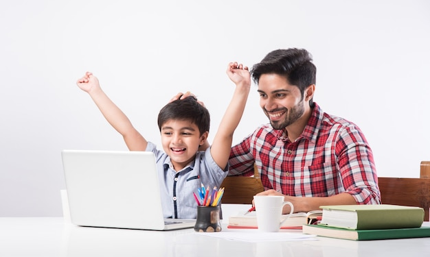 Menino indiano fofo com pai ou tutor masculino fazendo lição de casa em casa usando laptop e livros - conceito de ensino online