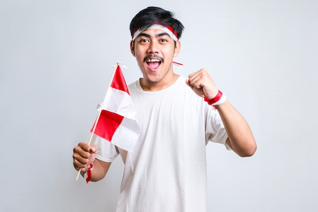 Menino indonésio fazendo o gesto de vitória e vitória, usando uma faixa vermelha e branca sobre fundo branco
